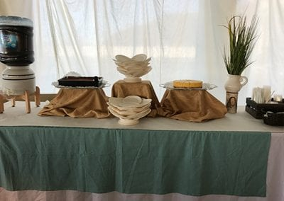 Table decorated green and white with set of plates and a cheesecake sliced