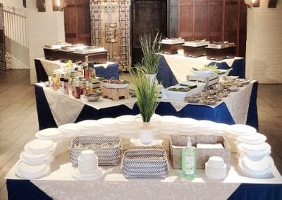 Tables decorated in blue and white with plates and condiments in them.
